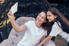 Lyckligt foto för moder- och dotterdanandeselfie vid vit minnestavla P Arkivfoto