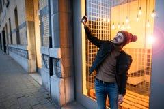 Lyckligt foto för selfie för hipstergrabbdanande mot bakgrunden av lampor Arkivfoto