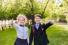 Lyckligt ge sig f?r skolbarn tummar upp royaltyfri bild