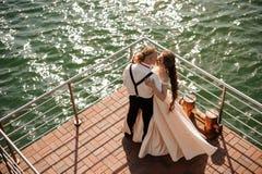 Lyckligt gift man- och kvinnaanseende på pir på sjön royaltyfria foton