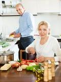 Lyckligt gift mognar par som tillsammans lagar mat i kök Royaltyfri Fotografi
