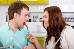 Lyckligt gift par matande sig med tomater royaltyfri bild