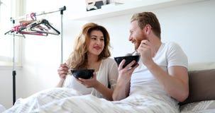 Lyckligt gift par som är romantiskt i säng som delar sädesslag royaltyfria bilder