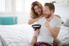 Lyckligt gift par som är romantiskt i säng som delar sädesslag royaltyfri bild