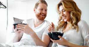 Lyckligt gift par som är romantiskt i säng som delar sädesslag royaltyfri foto