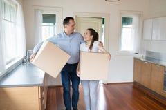 Lyckligt gift par som flyttar sig till det nya huset royaltyfri foto