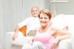 Lyckligt gift par som hemma kopplar av tillsammans arkivbilder