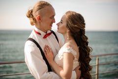 Lyckligt gift par som kramar i bakgrunden av havet arkivfoto