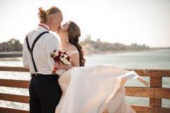 Lyckligt gift par som kysser på träbron i bakgrund av havet arkivbilder