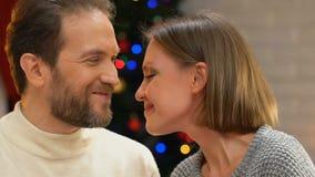 Lyckligt gift par som nuzzling och omfamnar som tycker om magisk julnatt arkivfilmer
