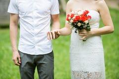 Lyckligt gift par som rymmer händer utomhus- med blommor royaltyfria foton