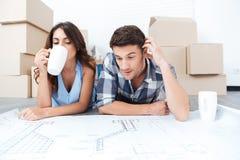 Lyckligt gift par som ser nya plana ritningar Arkivbild