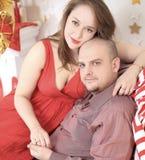 Lyckligt gift par som sitter på soffan på julnatt royaltyfria bilder