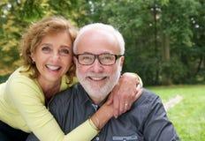 Lyckligt gift par som tillsammans utomhus ler royaltyfri foto