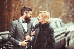 Lyckligt gift par som tycker om en antik bil för härlig dagoutdoorsat, en stilig förmögen man och hans ursnygga kvinnlig arkivfoton