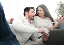 Lyckligt gift parsammanträde på soffan fotografering för bildbyråer
