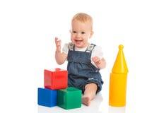 Lyckligt gladlynt barn som spelar med kvarterkuber på vit royaltyfri fotografi