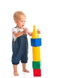 Lyckligt gladlynt barn som spelar med kvarterkuber som isoleras på vit Arkivbild