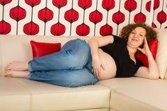 Lyckligt gravid koppla av på soffan Fotografering för Bildbyråer