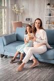 Lyckligt gravid kvinnahäleri som är närvarande från att att bry sig dottern Royaltyfri Bild