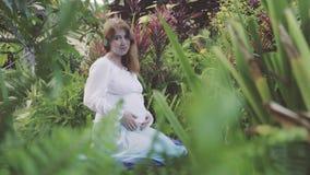Lyckligt gravid kvinnasammanträde på knä som kopplar av och tycker om liv i natur arkivfilmer
