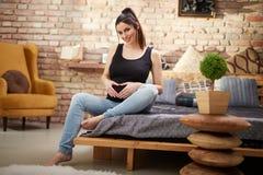 Lyckligt gravid kvinnasammanträde på säng hemma royaltyfri foto