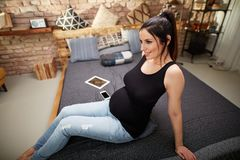 Lyckligt gravid kvinnasammanträde på säng hemma royaltyfria foton