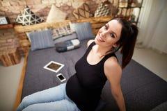 Lyckligt gravid kvinnasammanträde på säng hemma royaltyfri bild