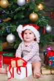 Lyckligt gulligt behandla som ett barn flickan i den Santa Claus hatten som hemma rymmer julgåvor på julträdet royaltyfria bilder