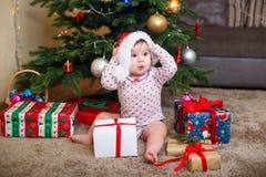 Lyckligt gulligt behandla som ett barn flickan i den Santa Claus hatten som hemma rymmer julgåvor på julträdet arkivbilder