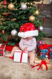Lyckligt gulligt behandla som ett barn flickan i den Santa Claus hatten som hemma rymmer julgåvor på julträdet royaltyfri bild