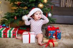 Lyckligt gulligt behandla som ett barn flickan i den Santa Claus hatten som hemma rymmer julgåvor på julträdet royaltyfria foton
