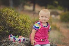 Lyckligt gulligt behandla som ett barn flickan med blonda hår som bär den rosa jeansklänningen som poserar att le i Central Park  Arkivfoto