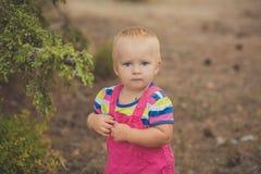 Lyckligt gulligt behandla som ett barn flickan med blonda hår som bär den rosa jeansklänningen som poserar att le i Central Park  Royaltyfri Bild