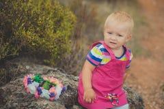 Lyckligt gulligt behandla som ett barn flickan med blonda hår som bär den rosa jeansklänningen som poserar att le i Central Park  Royaltyfria Foton