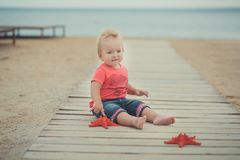 Lyckligt gulligt behandla som ett barn flickan med blonda hår och blåa ögon som bär stilfull kläder som poserar att le på strande Arkivbild