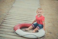 Lyckligt gulligt behandla som ett barn flickan med blonda hår och blåa ögon som bär stilfull kläder som poserar att le på strande Royaltyfri Foto