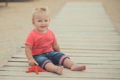 Lyckligt gulligt behandla som ett barn flickan med blonda hår och blåa ögon som bär stilfull kläder som poserar att le på strande Arkivbilder