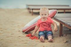 Lyckligt gulligt behandla som ett barn flickan med blonda hår och blåa ögon som bär stilfull kläder som poserar att le på strande Royaltyfria Bilder
