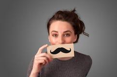 Lyckligt gulligt flickainnehavpapper med mustaschteckningen Royaltyfri Fotografi