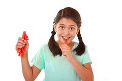 Lyckligt gulligt kvinnligt barn som slickar och äter den röda lakritsgodisen i begrepp för för ungeförälskelsesötsak och socker royaltyfria foton