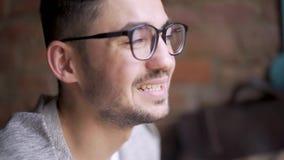 Lyckligt gulligt manligt högskolestudentsammanträde i ett kafé, blick på kameran och le4k stock video