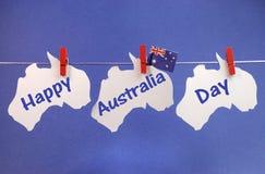 Lyckligt hälsa för Australien dagmeddelande som är skriftligt över vita australieröversikter och hängande pinnor för flagga på en  Royaltyfri Bild