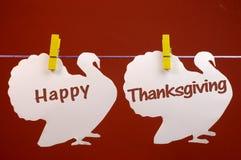 Lyckligt hälsa för tacksägelsemeddelande som är skriftligt över vita kalkon som hänger från pinnor på en linje Royaltyfri Foto