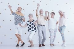 Lyckligt högt folk som dansar mot vit bakgrund med guld D arkivbild