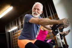 Lyckligt högt folk som gör övningar i idrottshall för att bli färdigt royaltyfria bilder