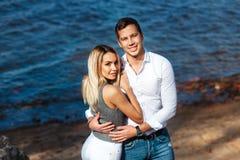 lyckligt hav för par Le lyckliga par som tillsammans ser kameran på sommarstranden Arkivfoto
