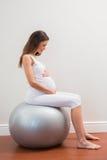 Lyckligt havandeskapsammanträde på exerciceboll Royaltyfri Fotografi