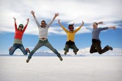 Lyckligt hoppa för vänner som är utomhus- Royaltyfri Fotografi
