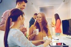 Lyckligt idérikt lag som dricker kaffe på kontoret royaltyfri bild